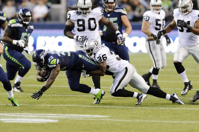 Aug 29, 2013; Seattle, WA, USA; Oakland Raiders defensive back Reggie Smith (36) tackles Seattle Seahawks running back Christine Michael (33) during the game at CenturyLink Field. Seattle defeated Oakland 22-6. Mandatory Credit: Steven Bisig-USA TODAY Sports