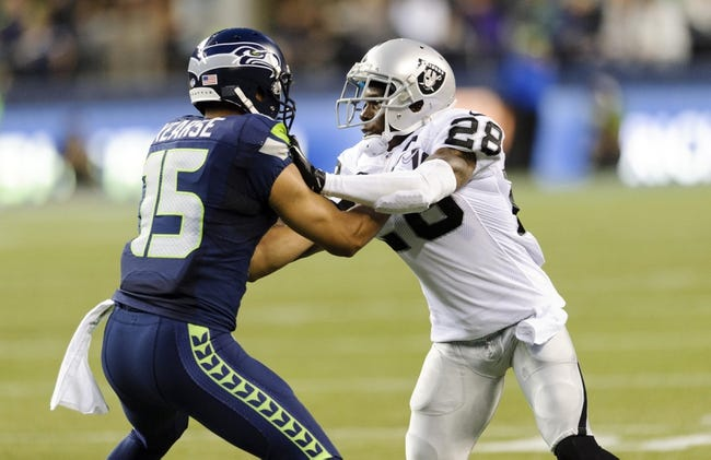 Aug 29, 2013; Seattle, WA, USA; Seattle Seahawks wide receiver Jermaine Kearse (15) blocks Oakland Raiders cornerback Phillip Adams (28) during the game at CenturyLink Field. Seattle defeated Oakland 22-6. Mandatory Credit: Steven Bisig-USA TODAY Sports