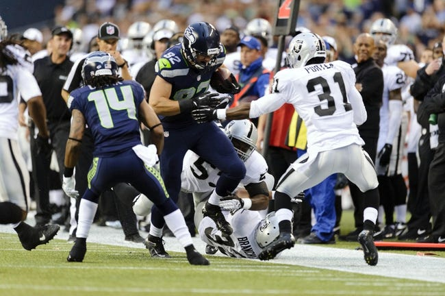 Aug 29, 2013; Seattle, WA, USA; Seattle Seahawks tight end Luke Willson (82) breaks a tackle by Oakland Raiders linebacker Omar Gaither (53) during the game at CenturyLink Field. Seattle defeated Oakland 22-6. Mandatory Credit: Steven Bisig-USA TODAY Sports