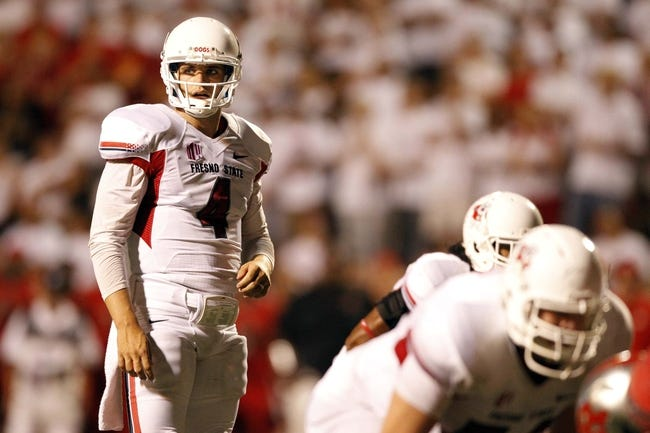 Aug 29, 2013; Fresno, CA, USA; Fresno State Bulldogs quarterback Derek Carr (4) prepares to take a snap against the Rutgers Scarlet Knights in the fourth quarter at Bulldog Stadium. The Bulldogs defeated the Scarlet Knights 52-51 in overtime. Mandatory Credit: Cary Edmondson-USA TODAY Sports