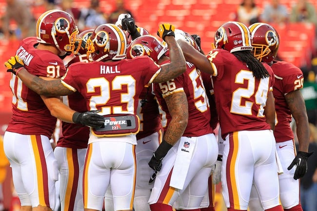 Aug 19, 2013; Landover, MD, USA; Washington Redskins players huddle on the field prior to their game against the Pittsburgh Steelers at FedEx Field. Mandatory Credit: Geoff Burke-USA TODAY Sports
