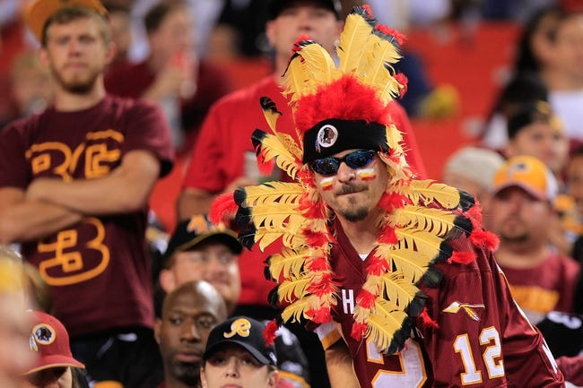 Aug 19, 2013; Landover, MD, USA; A Washington Redskins fan watches from the stands against the Pittsburgh Steelers at FedEx Field. Mandatory Credit: Geoff Burke-USA TODAY Sports
