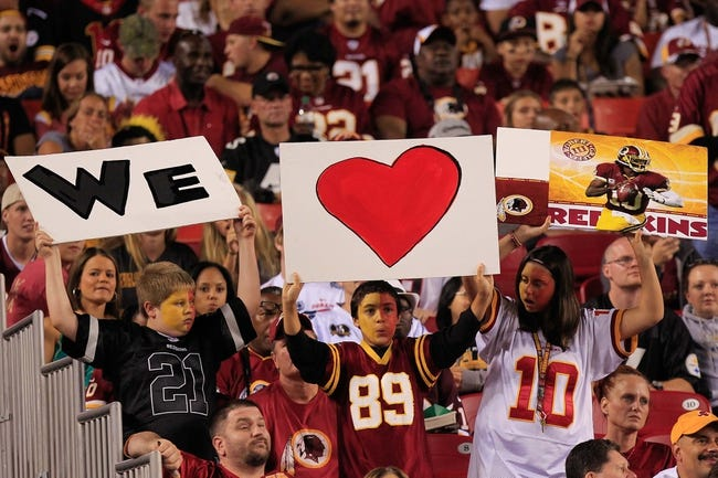 Aug 19, 2013; Landover, MD, USA; Washington Redskins fans hold signs in the stands against the Pittsburgh Steelers at FedEx Field. Mandatory Credit: Geoff Burke-USA TODAY Sports