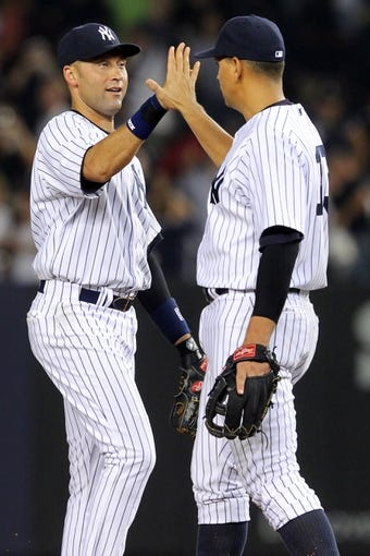 Aug 30, 2013; Bronx, NY, USA; New York Yankees shortstop Derek Jeter (2) and third baseman Alex Rodriguez (13) high five after defeating the Baltimore Orioles in a game at Yankee Stadium. Mandatory Credit: Brad Penner-USA TODAY Sports
