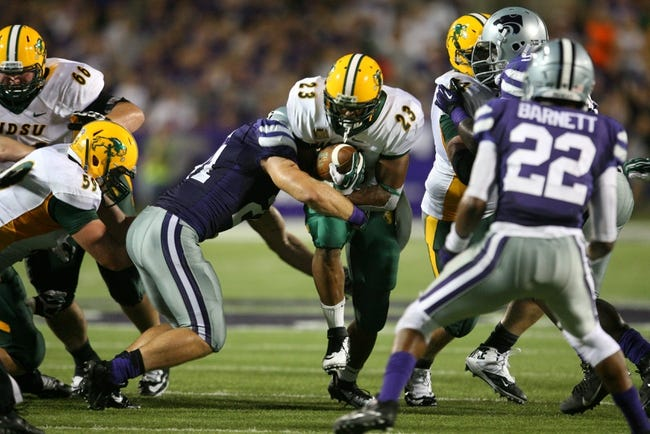 Aug 30, 2013; Manhattan, KS, USA; North Dakota State Bison running back John Crockett (23) is tackled by Kansas State Wildcats linebacker Jonathan Truman (21) during the Bisons' 24-21 win at Bill Snyder Family Stadium. Mandatory Credit: Scott Sewell-USA TODAY Sports