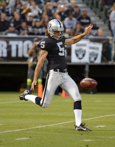 Aug 23, 2013; Oakland, CA, USA; Oakland Raiders punter Chris Kluwe (5) punts the ball during the game against the Chicago Bears at O.co Coliseum. Mandatory Credit: Kirby Lee-USA TODAY Sports