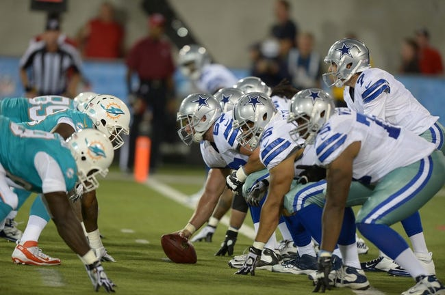Aug 4, 2013; Canton, OH, USA; General view of the line of scrimmage as Dallas Cowboys quarterback Alex Tanney (7) takes the snap from center Phil Costa (67) in the 2013 Hall of Fame Game against the Miami Dolphins at Fawcett Stadium. The Cowboys defeated the Dolphins 24-20. Mandatory Credit: Kirby Lee-USA TODAY Sports