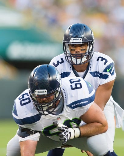 Aug 23, 2013; Green Bay, WI, USA; Seattle Seahawks quarterback Russell Wilson (3) lines up under center Max Unger (60) during the game against the Green Bay Packers at Lambeau Field.  Seattle won 17-10.  Mandatory Credit: Jeff Hanisch-USA TODAY Sports