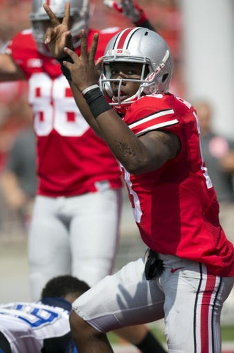 Aug 31, 2013; Columbus, OH, USA; Ohio State Buckeyes quarterback Kenny Guiton (13) celebrates a two-point conversion against the Buffalo Bulls at Ohio Stadium. Mandatory Credit: Greg Bartram-USA TODAY Sports