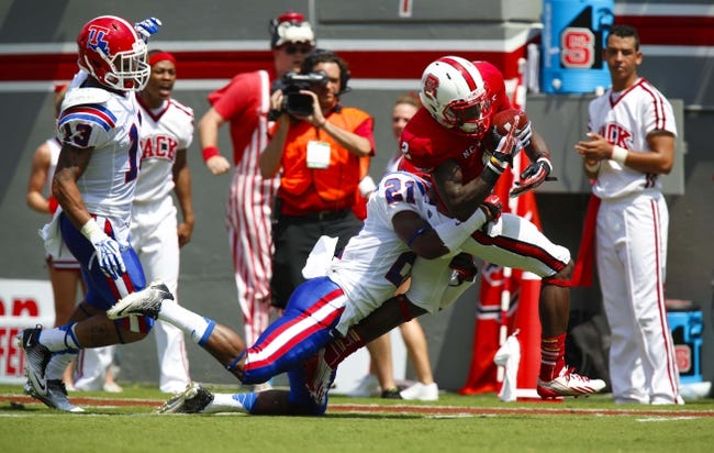 August 31, 2013; Raleigh, NC, USA;  North Carolina State wide receiver Rashard Smith (2) catches a 1st quarter pass in front of the Louisiana Tech defensive back Adairius Barnes (21) at Carter Finley Stadium. Mandatory Credit: James Guillory-USA TODAY Sports