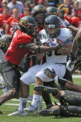 Aug 31, 2013; College Park, MD, USA; Maryland Terrapins defensive back Jeremiah Johnson (14) tackles Florida International Panthers running back Lamarq Caldwell (36) at Byrd Stadium. Mandatory Credit: Mitch Stringer-USA TODAY Sports