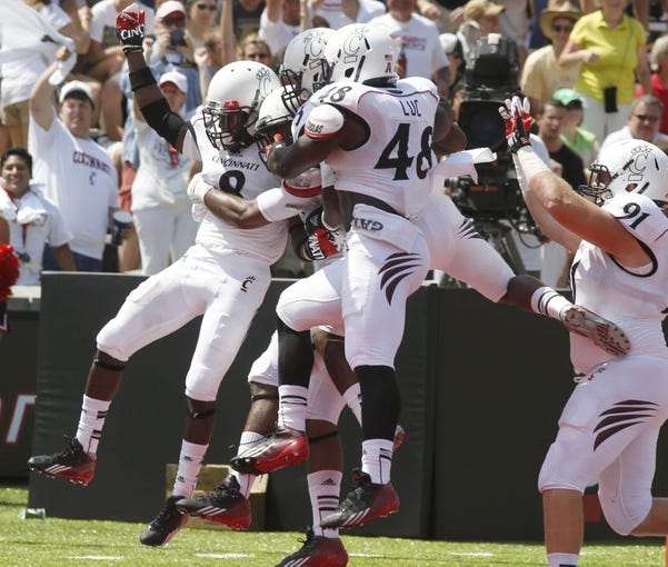 Aug 31, 2013; Cincinnati, OH, USA; Cincinnati Bearcats safety Adrian Witty (8) is congratulated by teammates in the end zone after he scored a 41 yard touchdown on an interception during the third quarter at Nippert Stadium. Cincinnati won 42-7. Mandatory Credit: David Kohl-USA TODAY Sports