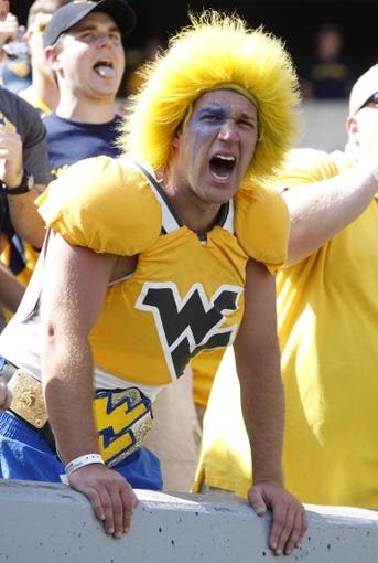 Aug 31, 2013; Morgantown, WV, USA; West Virginia Mountaineers fan Andy Loud cheers on the Montaineers against the William & Mary Tribe during the fourth quarter at Milan Puskar Stadium. The West Virginia Mountaineers won 24-17. Mandatory Credit: Charles LeClaire-USA TODAY Sports