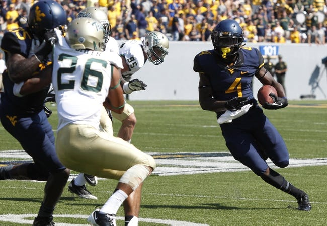 Aug 31, 2013; Morgantown, WV, USA; West Virginia Mountaineers running back Wendell Smallwood (4) carries the ball against the William & Mary Tribe during the fourth quarter at Milan Puskar Stadium. The West Virginia Mountaineers won 24-17. Mandatory Credit: Charles LeClaire-USA TODAY Sports