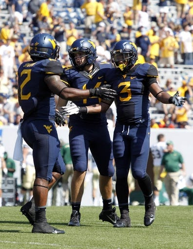 Aug 31, 2013; Morgantown, WV, USA; West Virginia Mountaineers running back Dreamius Smith (2) and quarterback Paul Millard (middle) and running back Charles Sims (3) celebrate after defeating the William & Mary Tribe at Milan Puskar Stadium. The West Virginia Mountaineers won 24-17. Mandatory Credit: Charles LeClaire-USA TODAY Sports
