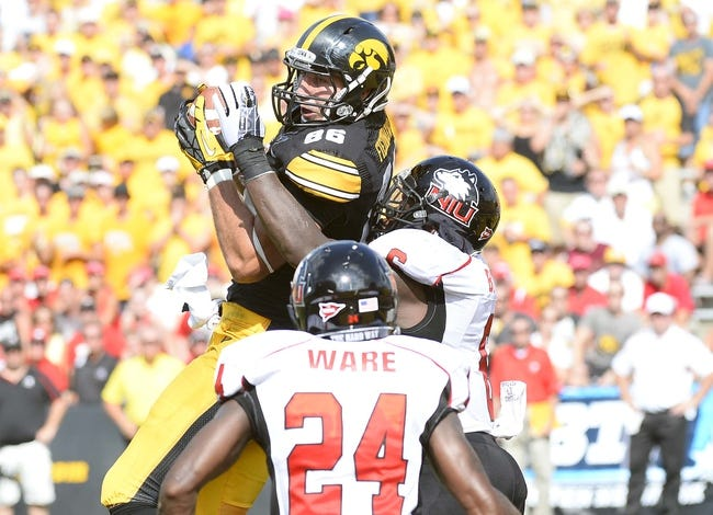 Aug 31, 2013; Iowa City, IA, USA; Iowa Hawkeyes tight end C.J. Fiedorowicz (86) makes a touchdown catch against Northern Illinois Huskies linebacker Jamaal Bass (6) during the second quarter at Kinnick Stadium. Mandatory Credit: Mike DiNovo-USA TODAY Sports