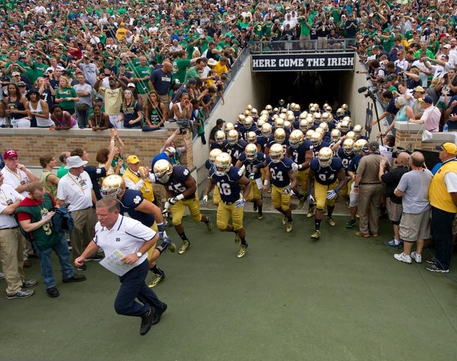 Aug 31, 2013; South Bend, IN, USA; Notre Dame Fighting Irish head coach Brian Kelly leads his players onto the field before the game against the Temple Owls at Notre Dame Stadium. Notre Dame won 28-6. Mandatory Credit: Matt Cashore-USA TODAY Sports