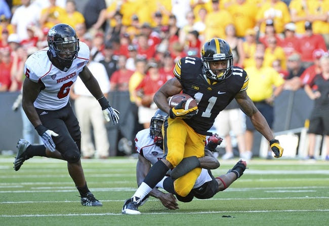 Aug 31, 2013; Iowa City, IA, USA; Northern Illinois Huskies wide receiver Juwan Brescacin (11) makes a catch against Northern Illinois Huskies linebacker Jamaal Bass (6) during the fourth quarter at Kinnick Stadium. Northern Illinois defeats Iowa 30-27. Mandatory Credit: Mike DiNovo-USA TODAY Sports