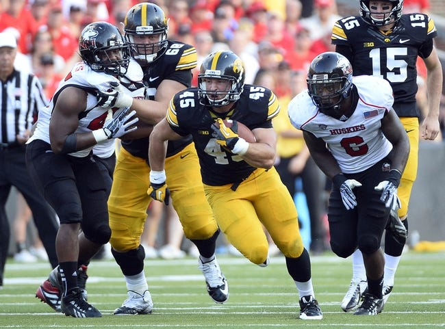 Aug 31, 2013; Iowa City, IA, USA; Iowa Hawkeyes fullback Mark Weisman (45) rushes the ball against Northern Illinois Huskies linebacker Jamaal Bass (6) during the fourth quarter at Kinnick Stadium. Northern Illinois defeats Iowa 30-27. Mandatory Credit: Mike DiNovo-USA TODAY Sports