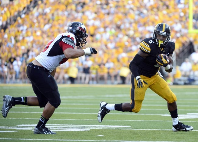 Aug 31, 2013; Iowa City, IA, USA; Iowa Hawkeyes running back Damon Bullock (5) rushes the ball against Northern Illinois Huskies defensive end Jason Meehan (49) during the fourth quarter at Kinnick Stadium. Northern Illinois defeats Iowa 30-27. Mandatory Credit: Mike DiNovo-USA TODAY Sports
