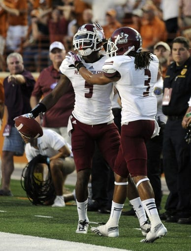 Aug 31, 2013; Austin, TX, USA; New Mexico State Aggies safety George Callender (5) and corner back Cameron Fuller react following an interception against the Texas Longhorns during the first half at Darrell K Royal-Texas Memorial Stadium. Mandatory Credit: Brendan Maloney-USA TODAY Sports