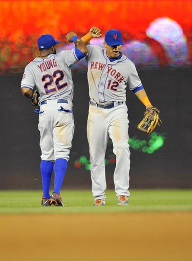 Aug 31, 2013; Washington, DC, USA; New York Mets teammates Eric Young (22) and Juan Lagares (12) celebrate after a game against the Washington Nationals at Nationals Park. The Mets defeated the Nationals 11-3. Mandatory Credit: Joy R. Absalon-USA TODAY Sports