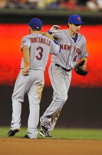 Aug 31, 2013; Washington, DC, USA; New York Mets teammates Omar Quintanilla (3) and Matt den Dekker (6) celebrate after a game against the Washington Nationals at Nationals Park. The Mets defeated the Nationals 11-3. Mandatory Credit: Joy R. Absalon-USA TODAY Sports
