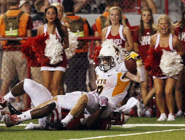 Aug 31, 2013; Lincoln, NE, USA; Wyoming Cowboys running back Brandon Miller (8) scores a touchdown against Nebraska Cornhuskers defender Randy Gregory (44) in the second half at Memorial Stadium. Mandatory Credit: Bruce Thorson-USA TODAY Sports