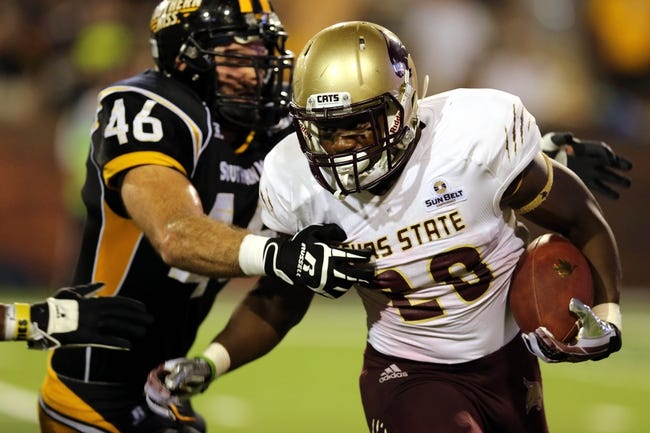 Aug 31, 2013; Hattiesburg, MS, USA; Texas State Bobcats running back Terrence Franks (20) is tackled by Southern Miss Golden Eagles defensive lineman Wil Freeman (46) in the third quarter at M.M. Roberts Stadium.Texas State won, 22-15. Mandatory Credit: Chuck Cook-USA TODAY Sports