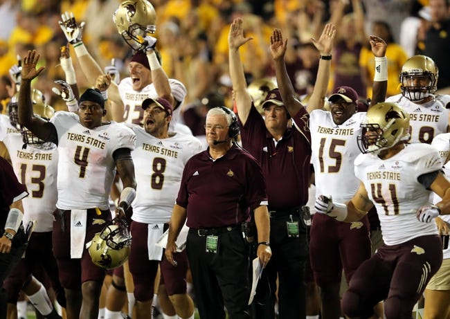 Aug 31, 2013; Hattiesburg, MS, USA; Texas State Bobcats head coach Dennis Franchione, center, and his bench watch quarterback Tyler Arndt (12) score the go-ahead touchdown to take a 20-15 lead at M.M. Roberts Stadium. Texas State won, 22-15. Mandatory Credit: Chuck Cook-USA TODAY Sports