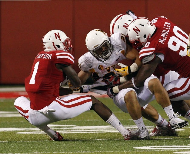 Aug 31, 2013; Lincoln, NE, USA; Nebraska Cornhuskers defenders Harvey Jackson (1) and Greg McMullen (90) tackle Wyoming Cowboys running back Shaun Wick (21) in the second half at Memorial Stadium. Nebraska won 37-34. Mandatory Credit: Bruce Thorson-USA TODAY Sports