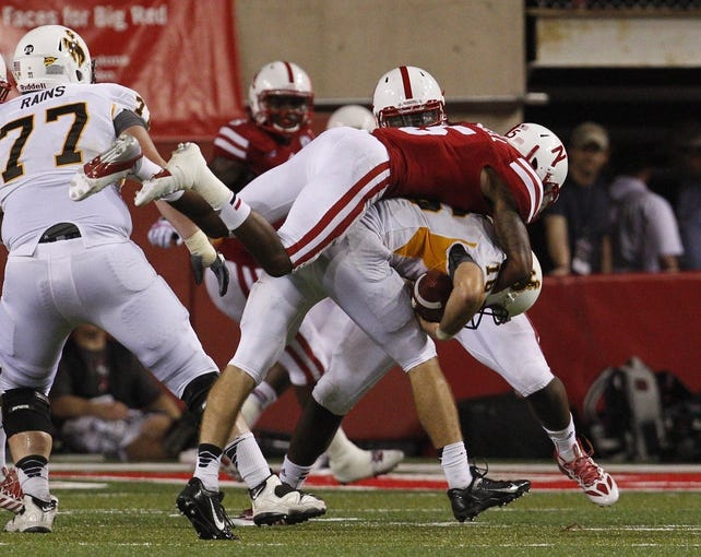 Aug 31, 2013; Lincoln, NE, USA; Nebraska Cornhuskers defender Josh Mitchell (5) sacks Wyoming Cowboys quarterback Brett Smith (16) in the second half at Memorial Stadium. Nebraska won 37-34. Mandatory Credit: Bruce Thorson-USA TODAY Sports