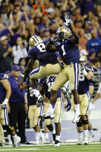 Aug 31, 2013; Seattle, WA, USA; Washington Huskies defensive end Hau'oli Kikaha (8) and Washington Huskies defensive back Sean Parker (1) celebrate after making a 3rd down stop against against the Boise State Broncos at Husky Stadium. Washington defeated Boise State 38-6. Mandatory Credit: Steven Bisig-USA TODAY Sports