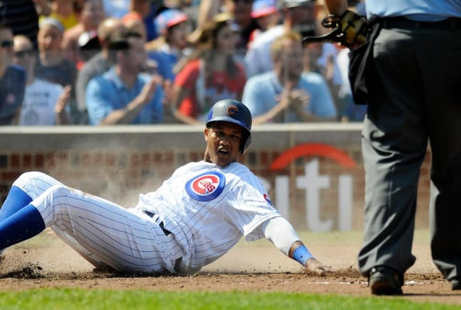 Sep 1, 2013; Chicago, IL, USA; Chicago Cubs shortstop Starlin Castro (13) slides into home plate on an RBI double by first baseman Anthony Rizzo (not pictured) during the third inning against the Philadelphia Phillies at Wrigley Field. Mandatory Credit: Reid Compton-USA TODAY Sports