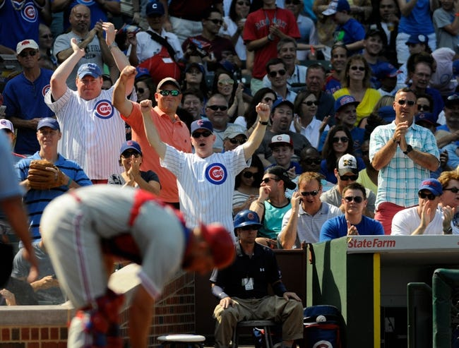 Sep 1, 2013; Chicago, IL, USA; Cubs fans celebrate after Chicago Cubs catcher Welington Castillo (53) is safe at home plate during the fourth inning against the Philadelphia Phillies at Wrigley Field. Mandatory Credit: Reid Compton-USA TODAY Sports