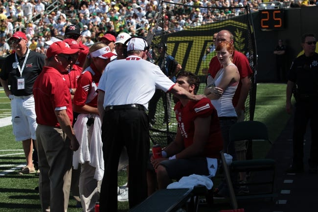 Aug 31, 2013; Eugene, OR, USA; Nicholls State Colonels head coach Charlie Stubbs checks on quarterback Beaux Hebert (11) following a targeting penatlly that ejected Oregon Ducks defensive back Terrance Mitchell (27) at Autzen Stadium. Mandatory Credit: Scott Olmos-USA TODAY Sports