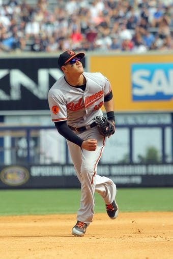 Aug 31, 2013; Bronx, NY, USA; Baltimore Orioles third baseman Manny Machado (13) tracks a pop fly against the New York Yankees during a game at Yankee Stadium. Mandatory Credit: Brad Penner-USA TODAY Sports