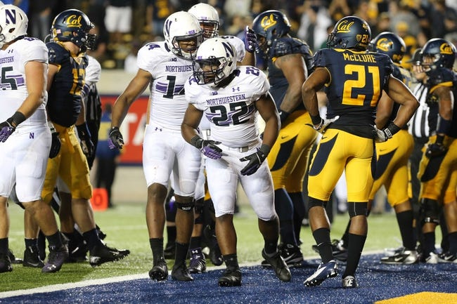Aug 31, 2013; Berkeley, CA, USA; Northwestern Wildcats running back Treyvon Green (22) returns to the sideline from under a pile after scoring a touchdown against the California Golden Bears during the fourth quarter at Memorial Stadium. Northwestern won 44-30. Mandatory Credit: Kelley L Cox-USA TODAY Sports