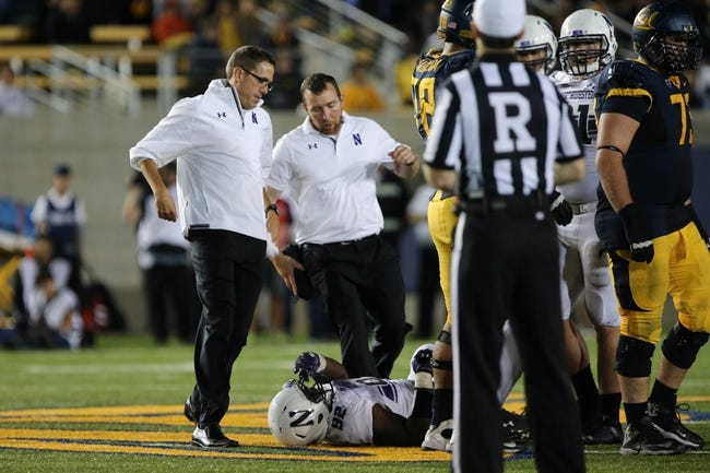 Aug 31, 2013; Berkeley, CA, USA; Northwestern Wildcats trainers tend to defensive lineman Tyler Scott (97) against the California Golden Bears during the fourth quarter at Memorial Stadium. Northwestern won 44-30. Mandatory Credit: Kelley L Cox-USA TODAY Sports
