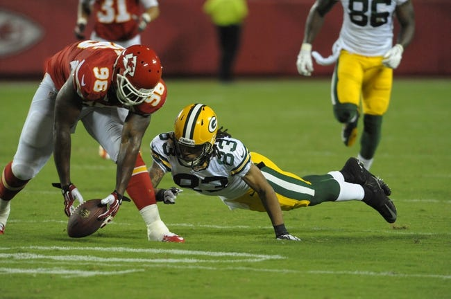 Aug 29, 2013; Kansas City, MO, USA; Green Bay Packers wide receiver Ty Walker (83) fumbles the ball as Kansas City Chiefs defensive end Marcus Dixon (96) attempts to recover during the first half of the game at Arrowhead Stadium. The Chiefs won 30-8. Mandatory Credit: Denny Medley-USA TODAY Sports