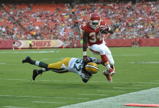 Aug 29, 2013; Kansas City, MO, USA; Kansas City Chiefs running back Knile Davis (34) is pushed out of bounds by Green Bay Packers tackle Don Barclay (67) during the first half of the game against the Green Bay Packers at Arrowhead Stadium. The Chiefs won 30-8. Mandatory Credit: Denny Medley-USA TODAY Sports