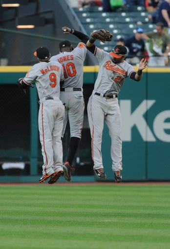 Sep 2, 2013; Cleveland, OH, USA; Baltimore Orioles left fielder Nate McLouth (9), center fielder Adam Jones (10) and right fielder Nick Markakis (21) celebrate the Orioles 7-2 over the Cleveland Indians at Progressive Field. Mandatory Credit: Ken Blaze-USA TODAY Sports