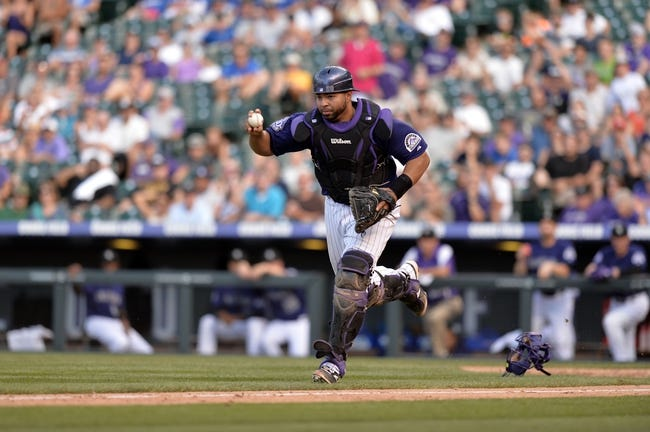 Sept 2, 2013; Denver, CO, USA; Colorado Rockies catcher Wilin Rosario (20) in a rundown of the Los Angeles Dodgers at Coors Field. The Dodgers defeated the Rockies 10-8. Mandatory Credit: Ron Chenoy-USA TODAY Sports