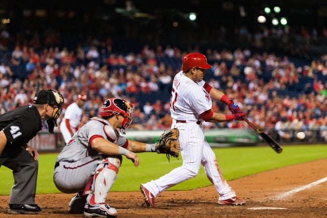 Sep 2, 2013; Philadelphia, PA, USA; Philadelphia Phillies catcher Carlos Ruiz (51) hits an RBI single during the ninth inning against the Washington Nationals at Citizens Bank Park. The Phillies defeated the Nationals 3-2. Mandatory Credit: Howard Smith-USA TODAY Sports
