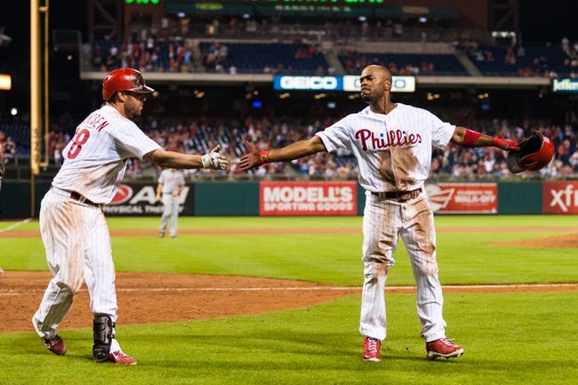 Sep 2, 2013; Philadelphia, PA, USA; Philadelphia Phillies shortstop Jimmy Rollins (11) celebrates scoring with first baseman Kevin Frandsen (28) during the eighth inning against the Washington Nationals at Citizens Bank Park. The Phillies defeated the Nationals 3-2. Mandatory Credit: Howard Smith-USA TODAY Sports