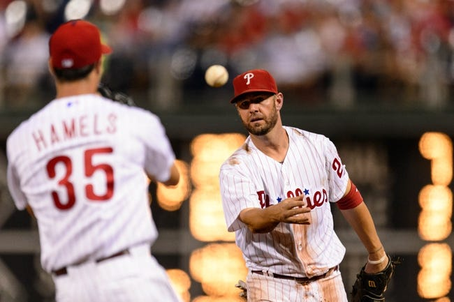 Sep 2, 2013; Philadelphia, PA, USA;  Philadelphia Phillies first baseman Kevin Frandsen (28) tosses the ball to pitcher Cole Hamels (35) covering first bar during the sixth inning against the Washington Nationals at Citizens Bank Park. The Phillies defeated the Nationals 3-2. Mandatory Credit: Howard Smith-USA TODAY Sports