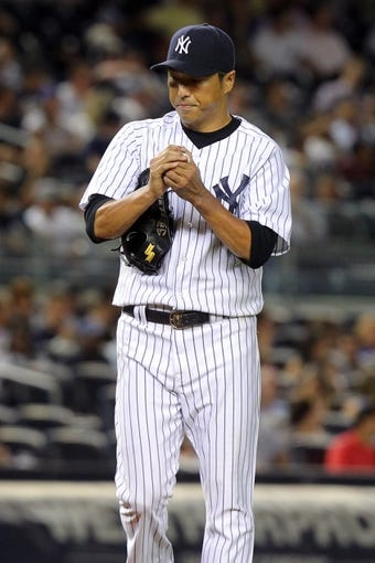 Sep 3, 2013; Bronx, NY, USA; New York Yankees starting pitcher Hiroki Kuroda (18) reacts after allowing two runs to score on a triple by Chicago White Sox shortstop Alexei Ramirez (not pictured) during the fifth inning of a game at Yankee Stadium. Mandatory Credit: Brad Penner-USA TODAY Sports