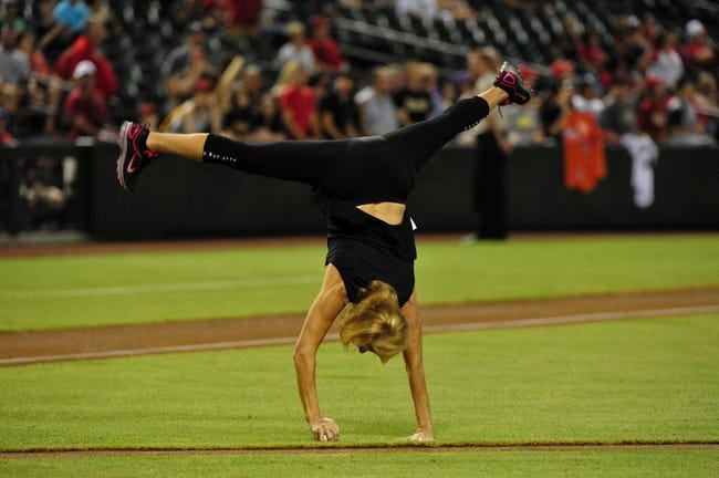 Sept 3, 2013; Phoenix, AZ, USA; Four time Olympic gold medalist in gymnastics Olga Korbut does a cartwheel prior to throwing out the first pitch for the game between the Arizona Diamondbacks and the Toronto Blue Jays at Chase Field. Mandatory Credit: Matt Kartozian-USA TODAY Sports