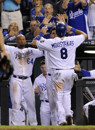 Sep 3, 2013; Kansas City, MO, USA; Kansas City Royals third baseman Mike Moustakas (8) is congratulated by second baseman Emilio Bonifacio (64) after scoring against the Seattle Mariners in the eight inning at Kauffman Stadium. The Royals won the game 4-3. Mandatory Credit: John Rieger-USA TODAY Sports