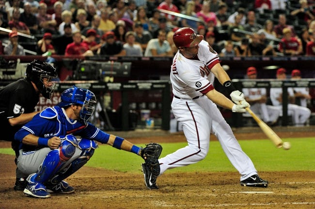 Sept 3, 2013; Phoenix, AZ, USA; Arizona Diamondbacks first baseman Paul Goldschmidt (44) hits a single as Toronto Blue Jays catcher J.P. Arencibia (9) looks on during the fourth inning at Chase Field. Mandatory Credit: Matt Kartozian-USA TODAY Sports